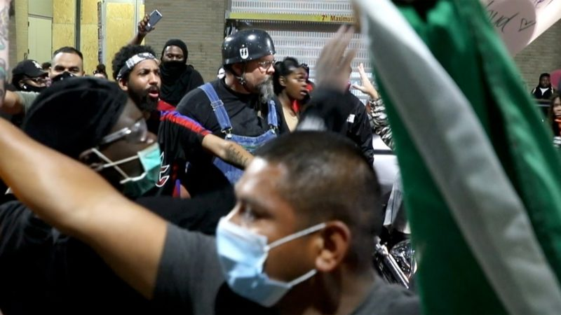 Demonstrators confront biker during protest
