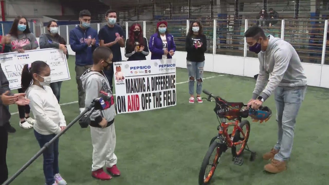 Student athletes surprise kids with bikes, cash as part of national day of service